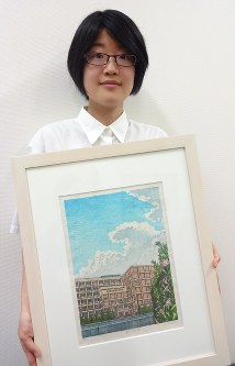 母校・新宿高を描いた自身の作品を持つ百瀬さん=同校で