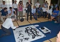 石飛博光さん(左手前)の揮毫を見守る駐日14カ国外交団の人たち=佐久市の貞祥寺で