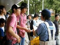 歩きながらスマホを使わないよう呼び掛ける中署員=名古屋市昭和区の鶴舞公園入り口付近で