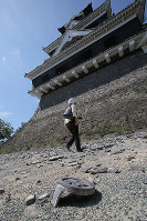 The main tower of Kumamoto Castle, with roof tiles that fell in the Kumamoto Earthquake lying around it, is seen in Kumamoto on July 28, 2016. (Mainichi)