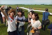 公開試験飛行の合間に展示される、「メーヴェ」をモデルにした飛行機と記念撮影する女性たち。機体の周囲には人だかりができていた=北海道滝川市のたきかわスカイパークで2016年7月31日午前8時13分、手塚耕一郎撮影