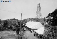 名古屋城再建。組み立てられた大やぐらの下で起工式 。起工式の参列者を驚かそうと、起工式前夜の12日午後10時半ごろまで1日半がかりで急きょ大やぐらを建てた。高さは焼けた天守閣のシャチの先端までと同じ=1957(昭和32)年6月13日