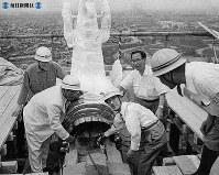 大天守閣頂上でオスの金シャチのボルトを締める小林市長(中央)=1959(昭和34)年8月8日