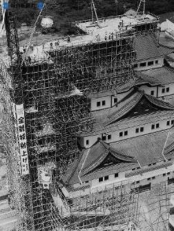 日の丸の旗をつけた重さ2トンのシャチの入った鉄ワクはウインチの力でゆっくりと上がる オスは1959(昭和34)年3月21日、メスは8月2日、大阪から東海道をお国入りした。値段はいずれも約2400万円。8月5日にまずメスが3時間がかりの作業で高さ48.27メートルの大天守閣頂上に据えつけられた。続いて6日、オスの取り付けを終われば名古屋城の再建工事はほとんど完成、10月1日の完成式を待つばかり=1959(昭和34)年8月5日