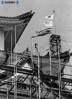 """1959(昭和34)年5月29日朝、大天守閣のてっぺんにオリンピック旗がはためいた この五輪旗は""""東京オリンピック決定を祝って""""間組が掲げたもの。「名古屋市民にも見てもらいましょう」ということだった。しかし、「お城は広告塔じゃないんだから」と、午後3時過ぎには降ろされてしまった=1959(昭和34)年5月29日"""