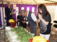 白菊を献花し手を合わせる遺族ら=京都府東山区の霊山観音で、礒野健一撮影
