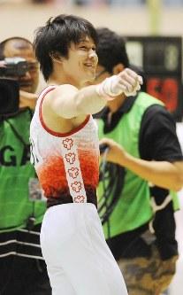NHK杯で優勝が決まり客席に向かって笑顔で右腕を掲げる内村航平=東京・国立代々木競技場で2009年6月7日、内藤絵美撮影