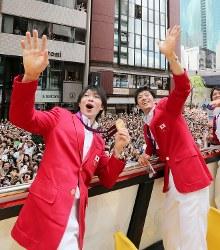 沿道の歓声に手を振る体操男子の内村航平(左)と田中和仁=東京・銀座で2012年8月20日午前11時17分、(代表撮影)