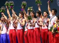 男子団体で金メダルを獲得し、表彰台で笑顔を見せる内村航平(右から3人目)ら日本の選手たち=イギリス・グラスゴーで2015年10月28日、小川昌宏撮影