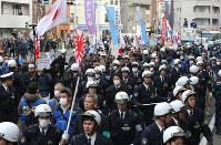 大勢の警察官に囲まれ、差別的言動を叫びながら歩くヘイトスピーチデモの参加者たち=川崎市川崎区で2016年1月31日、後藤由耶撮影