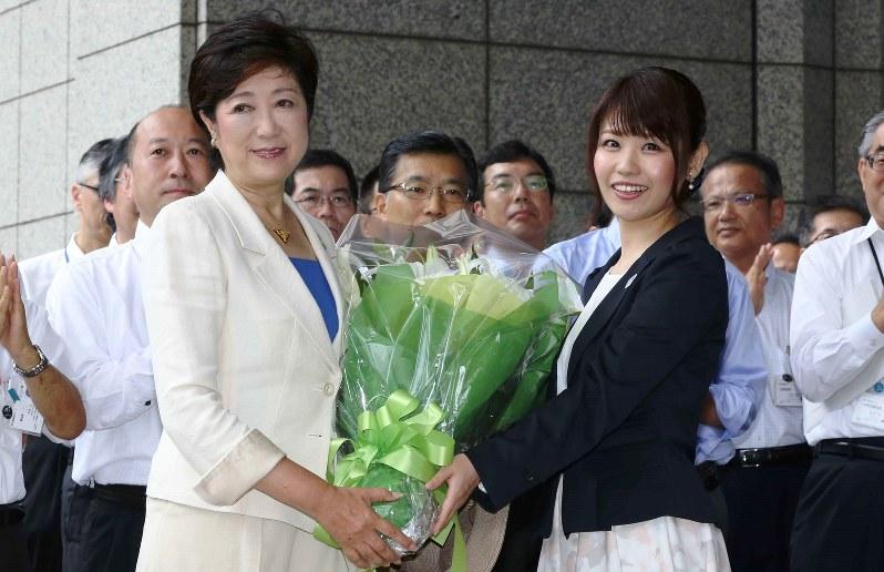 登庁し、花束を贈られて笑顔を見せる小池百合子・新東京都知事(左)=2016年8月2日
