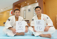 Judoka Naohisa Takato, left, and Masashi Ebinuma hold up placards with their aspirations for the year -- reading