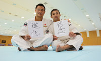 Judoka Naohisa Takato, right, and Masashi Ebinuma hold up placards with their aspirations for the year, at the Ajinomoto National Training Center in Tokyo's Kita Ward on Jan. 6, 2015. (Mainichi)