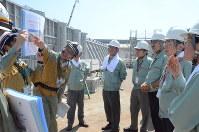 4号機の取水槽の溢水防止壁の前で、中部電力の担当者から壁の構造について説明を受ける県防災・原子力学術会議の委員ら=御前崎市の中部電力浜岡原発で