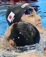 競泳男子400メートル個人メドレー決勝で優勝した萩野(手前)を抱き合って祝福する瀬戸=リオデジャネイロの五輪水泳競技場で2016年8月6日、山本晋撮影