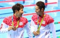 競泳男子400メートル個人メドレーの表彰式を終え、笑顔で言葉を交わす優勝した萩野公介(右)と3位の瀬戸大也=ブラジル・リオデジャネイロの五輪水泳競技場で2016年8月6日、小川昌宏撮影