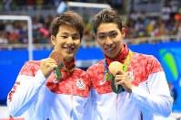 金メダルと銅メダルを胸に喜び合う萩野公介(右)と瀬戸大也=リオデジャネイロの五輪水泳競技場で2016年8月6日、梅村直承撮影