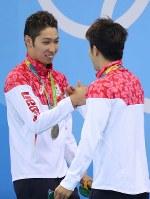 競泳男子400メートル個人メドレーの表彰式を終え、メダルを胸に握手を交わす優勝した萩野公介(左)と3位の瀬戸大也=ブラジル・リオデジャネイロの五輪水泳競技場で2016年8月6日、小川昌宏撮影