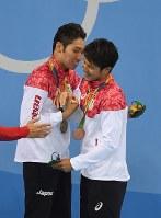 競泳男子400メートル個人メドレー決勝の表彰式でお互いの健闘をたたえ合う金メダルの萩野公介(左)と銅メダルの瀬戸大也=リオデジャネイロの五輪水泳競技場で2016年8月6日、三浦博之撮影