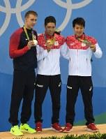 競泳男子400メートル個人メドレー決勝で金メダルを獲得し、表彰台で笑顔を見せる萩野公介(中央)と銅メダルの瀬戸大也(右)。左は銀メダルのチェース・ケイリシュ=リオデジャネイロの五輪水泳競技場で2016年8月6日、三浦博之撮影