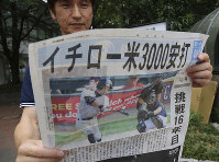 A man reads an extra edition of a Japanese newspaper reporting Miami Marlins' Ichiro Suzuki's 3,000th career hit in the major leagues, in Tokyo, on Aug. 8, 2016. (AP Photo/Koji Sasahara)