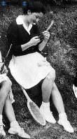 日本郵船飛田給体育場テニスコートで行われたトーナメントでプレー後、ともに出場していた皇太子さまから贈られたお土産の粽(ちまき)を手にしてうれしそうに見る美智子さま=1958年(昭和33年)5月4日撮影
