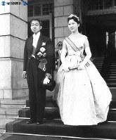 「結婚の儀」「朝見の儀」終了後、報道機関の撮影のため宮内庁正面玄関に立つ皇太子さまと美智子さま=1959年(昭和34年)4月10日撮影