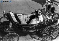 東宮仮御所へ向かうパレードの最中、沿道のビルからの歓呼に応える皇太子さまと美智子さま=1959年(昭和34年)4月10日撮影