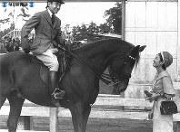 馬術の障害レースに出場した皇太子さま。結果が振るわず美智子さまに調子を聞かれて馬上から笑い返す。美智子さまが手に持っているのは宮内庁管理部車馬課の「朝萩号」をいたわる餌のニンジン=1961年(昭和36年)11月5日撮影