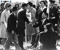 東京の代々木公園陸上競技場で開かれた第2回パラリンピック東京大会の開会式で、フィールドに降りて各国選手代表に励ましの言葉を掛け握手する大会名誉会長の皇太子さまと美智子さま=1964年(昭和39年)11月8日撮影