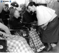 伊豆大島の三原山噴火による全島避難で、東京都老人医療センター(東村山市)に収容された「社会福祉法人養和会大島老人ホーム」の車椅子のお年寄りを見舞い、言葉を掛けて励ます美智子さま=1986年(昭和61年)12月5日撮影