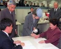 触読校閲の藤野美智子さんの手をさすり、声をかける皇后さま=毎日新聞大阪本社の点字毎日編集室で1999年(平成11年)11月17日、玉置勝巳撮影