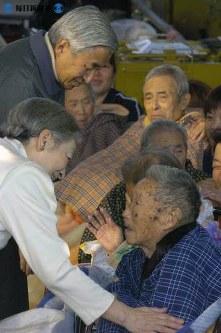 新潟県中越地震で、新潟県小千谷市の同市総合体育館で被災者に話しかける両陛下=2004年(平成16年)11月6日、小関勉撮影
