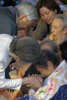 新潟県中越地震で被災したお年寄りは、皇后さまに話しかけられた後、ぎゅっと手を握りしめた=新潟県小千谷市の小千谷市総合体育館で2004年(平成16年)11月6日、小関勉撮影