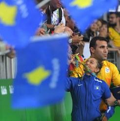 コソボ国旗を振る観客席の応援団に金メダルを見せる柔道女子52キロ級のマイリンダ・ケルメンディ=リオデジャネイロのカリオカアリーナで2016年8月7日、和田大典撮影