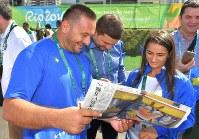 半年ほど前の取材時の写真と記事が掲載された毎日新聞の紙面に笑顔を見せる柔道女子コソボ代表のケルメンディ(右手前)とコーチのクカさん=リオデジャネイロの選手村で2016年8月4日、和田大典撮影