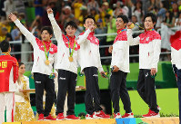 From left, Koji Yamamuro, Kohei Uchimura, Yusuke Tanaka, Kenzo Shirai and Ryohei Kato show off their gold medals on the podium during the medal ceremony at the Rio Olympics at the Rio Olympic Arena in Rio de Janeiro on Aug. 8, 2016. (Mainichi)