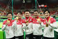 From left, Koji Yamamuro, Kohei Uchimura, Yusuke Tanaka, Kenzo Shirai and Ryohei Kato pose with their gold medals for the men's team all-around at the Rio Olympics at the Rio Olympic Arena in Rio de Janeiro on Aug. 8, 2016. (Mainichi)
