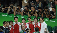 Japan's gymnastics team waits for their marks in the team all-around while watching the scoreboard at the Rio Olympics at the Rio Olympic Arena in Rio de Janeiro on Aug. 8, 2016. (Mainichi)