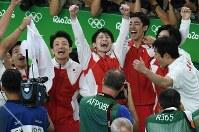 体操男子団体総合で金メダルが確定し、ガッツポーズで喜ぶ内村航平(中央)ら=リオデジャネイロのリオ五輪アリーナで2016年8月8日、三浦博之撮影