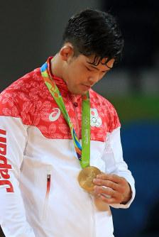 柔道男子73キロ級の表彰式で、胸に掛けられた金メダルを見つめる大野将平=リオデジャネイロのカリオカアリーナで2016年8月8日、梅村直承撮影