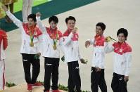 体操男子団体総合で金メダルを獲得し、観客席の声援に応える内村航平(左から2人目)ら=リオデジャネイロのリオ五輪アリーナで2016年8月8日、三浦博之撮影
