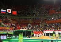 体操男子団体決勝での優勝が決まり、掲揚される日の丸を見つめる日本の選手ら=リオデジャネイロのリオ五輪アリーナで2016年8月8日、小川昌宏撮影