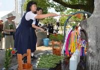 原爆犠牲者慰霊平和祈念碑に水をかける生徒ら