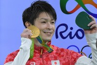 Gymnast Kohei Uchimura shows his gold medal in the men's individual all-around to his fans in the stands at the Rio Olympic Arena, on Aug. 10. 2016. (Mainichi Photo/Daisuke Wada)