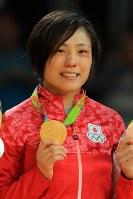 目に涙を浮かべ表彰台で金メダルを手にする女子70キロ級の田知本遥=リオデジャネイロのカリオカアリーナで2016年8月10日、梅村直承撮影