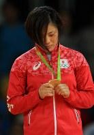 表彰台で金メダルを見つめる女子70キロ級の田知本遥=リオデジャネイロのカリオカアリーナで2016年8月10日、梅村直承撮影