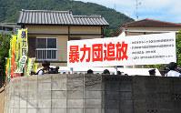 暴力団を監視するため、兵庫県警が設置した特別警戒所(左奥)と暴力団追放を訴える看板=神戸市灘区で