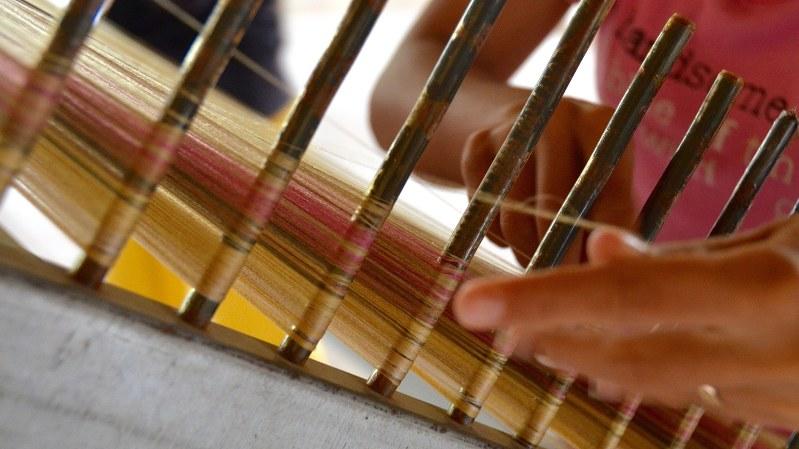 縦糸を巻きつけるカンボジアの手織り職人=小高朋子撮影