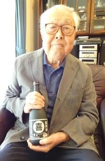 卒業生から贈られた再会記念のボトルを手にしてほほ笑む佐藤さん=多摩市の自宅で
